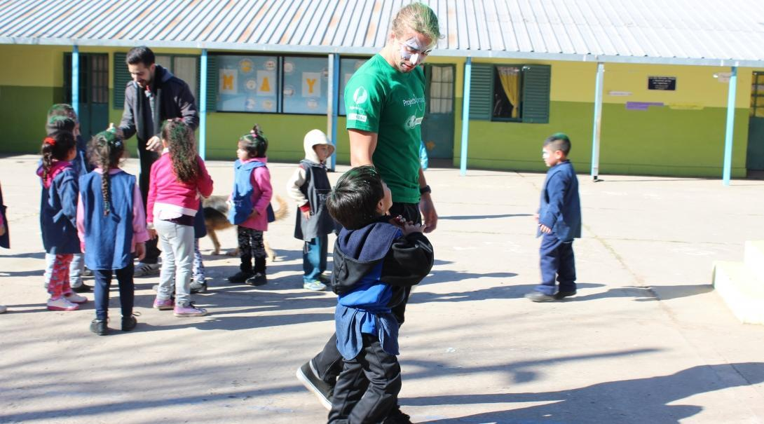 A child talks to a Projects Abroad Childcare volunteer during an outdoor activity at a kindergarten in Argentina.